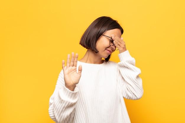 Молодая латинская женщина закрывает лицо рукой и поднимает другую руку, чтобы остановиться, отказываясь от фотографий или изображений
