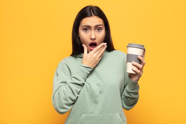 Молодая латинская женщина закрывает рот руками с шокированным, удивленным выражением лица, хранит секрет или говорит: ой