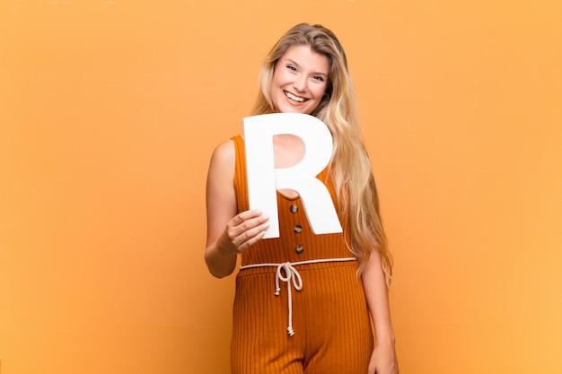 Молодая латинская женщина взволнована, счастлива, радостна, держа букву r алфавита, чтобы сформировать слово или предложение.