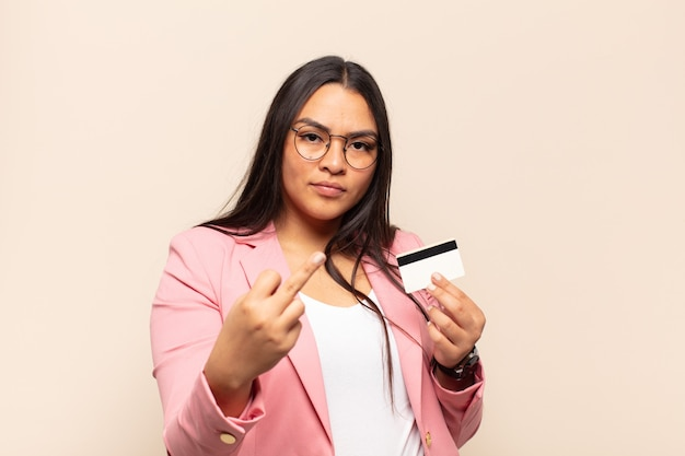 Young latin woman feeling angry, annoyed, rebellious and aggressive, flipping the middle finger, fighting back