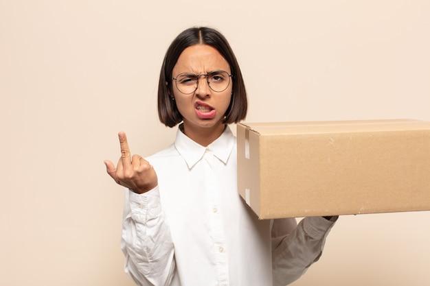 Молодая латинская женщина чувствует себя сердитой, раздраженной, мятежной и агрессивной, переворачивает средний палец, сопротивляется