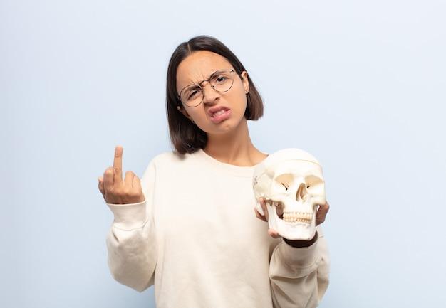 화가 나고, 짜증이 나고, 반항적이고 공격적인 느낌, 가운데 손가락을 뒤집고, 반격하는 젊은 라틴 여자
