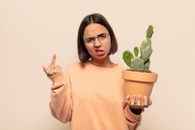 若いラテン女性は、怒り、イライラ、反抗的、攻撃的、中指をひっくり返し、反撃を感じています