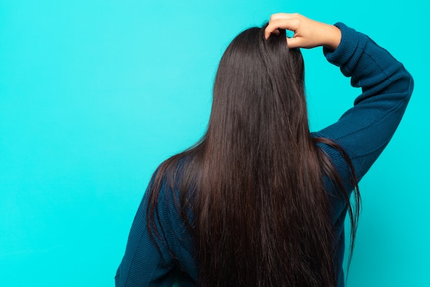 腰に手を、頭に他の手を持って、解決策を考えて、無知で混乱している若いラテン女性、背面図