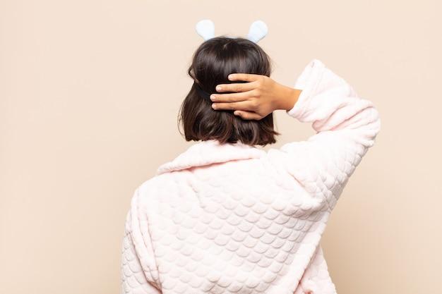 若いラテン女性は無知で混乱していると感じ、解決策を考え、腰に手を、頭に他の手を、背面図