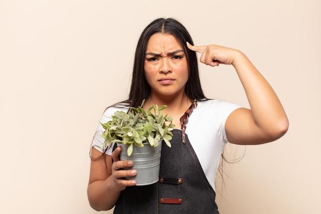 Молодая латинская женщина смущена и озадачена, показывая, что вы сумасшедшие, сумасшедшие или в своем уме
