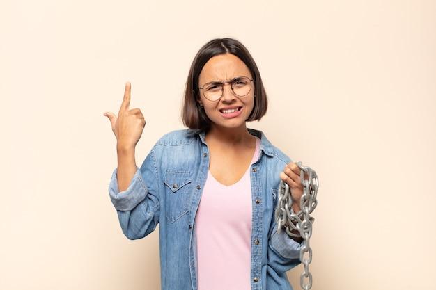 혼란스럽고 의아해하는 젊은 라틴 여성, 당신이 미쳤거나 미쳤거나 정신이 나갔음을 보여줍니다.