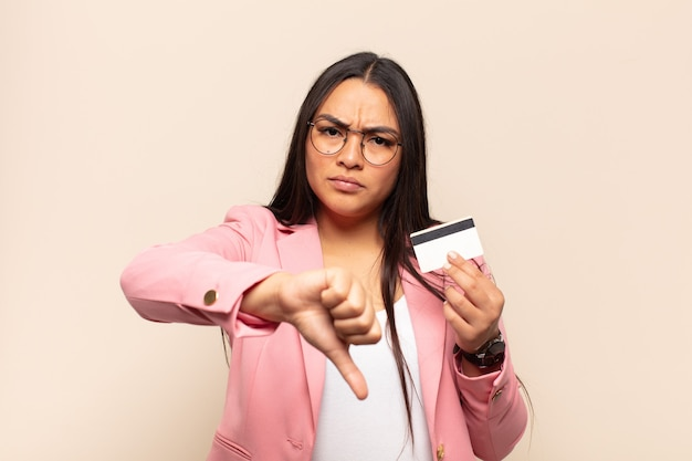 Young latin woman feeling cross, angry, annoyed, disappointed or displeased, showing thumbs down with a serious look