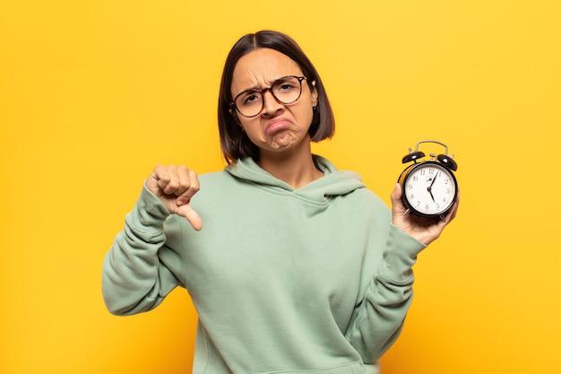 심각한 표정으로 아래로 엄지 손가락을 보여주는 십자가, 분노, 짜증, 실망 또는 불쾌감을 느끼는 젊은 라틴 여자