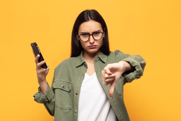 若いラテン女性は、真剣な表情で親指を下に見せて、十字架、怒り、イライラ、失望または不満を感じています