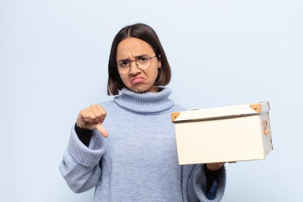 Молодая латинская женщина чувствует себя раздраженной, сердитой, раздраженной, разочарованной или недовольной, показывая большие пальцы вниз с серьезным взглядом