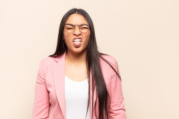 Молодая латинская женщина чувствует отвращение и раздражение, высовывает язык, не любит что-то противное и противное