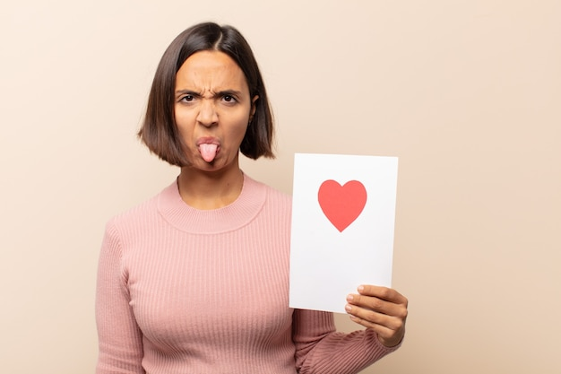 若いラテン女性は嫌悪感とイライラを感じ、舌を突き出し、厄介で厄介なものを嫌います