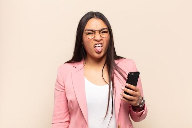 젊은 라틴 여성은 역겨움과 짜증을 느끼고 혀를 내밀고 불쾌하고 불쾌한 것을 싫어합니다.