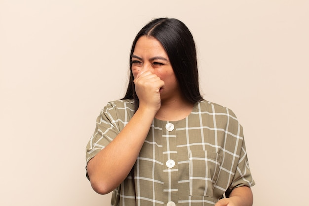 Young latin woman feeling disgusted, holding nose to avoid smelling a foul and unpleasant stench