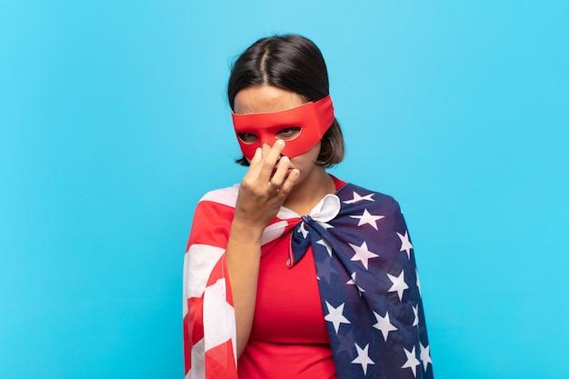 Молодая латинская женщина чувствует отвращение, зажимая нос, чтобы не почувствовать неприятный и неприятный запах