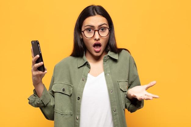 若いラテン女性は、ストレスと恐怖の表情で、非常にショックを受け、驚き、不安とパニックを感じています
