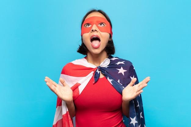 Молодая латинская женщина чувствует себя счастливой, пораженной, удачливой и удивленной, празднует победу с поднятыми руками