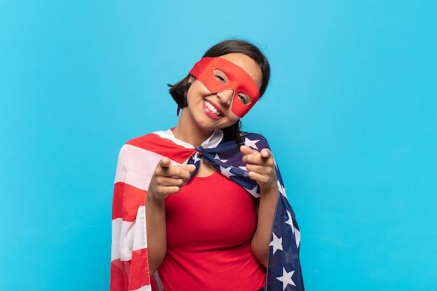 Молодая латинская женщина чувствует себя счастливой и уверенной, указывая на камеру обеими руками и смеясь, выбирая вас