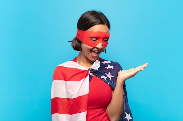 横に手に持っているオブジェクトやコンセプトを見て、幸せとさりげなく笑顔を感じている若いラテン女性