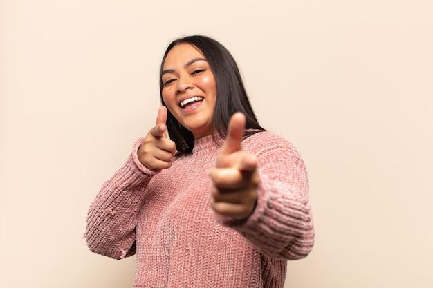 Молодая латинская женщина чувствует себя счастливой, крутой, удовлетворенной, расслабленной и успешной, указывая на камеру, выбирая вас