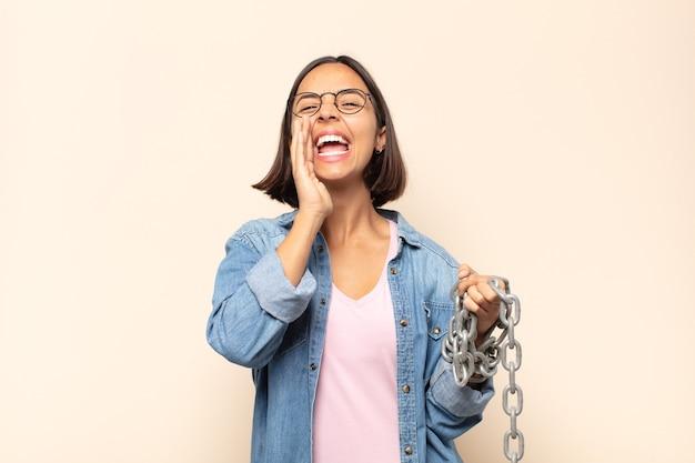 Молодая латинская женщина чувствует себя счастливой, взволнованной и позитивной, громко кричит, прижав руки ко рту, выкрикивая