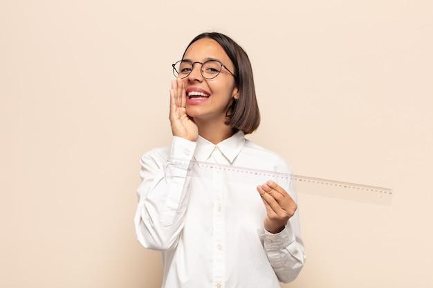 Молодая латинская женщина чувствует себя счастливой, взволнованной и позитивной, громко кричит, держа руки у рта