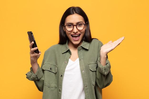 Молодая латинская женщина чувствует себя счастливой, взволнованной, удивленной или шокированной, улыбается и удивляется чему-то невероятному
