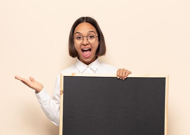 행복하고, 흥분되고, 놀라거나 충격을 받고, 웃고, 믿을 수없는 것에 놀란 젊은 라틴 여자