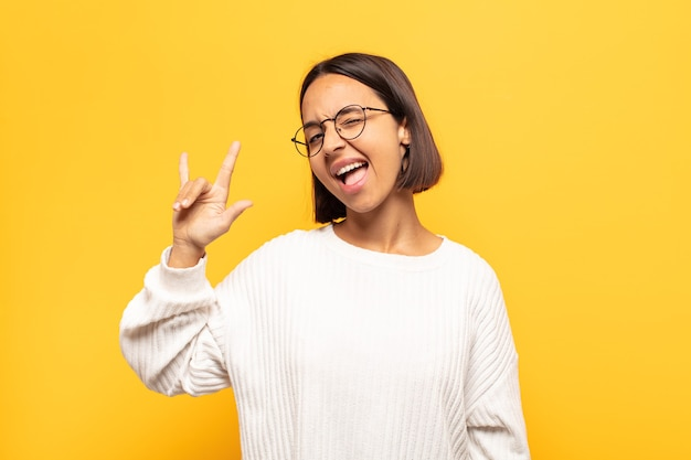 Молодая латинская женщина чувствует себя счастливой, веселой, уверенной, позитивной и мятежной, делая знак рок или хэви-метал рукой