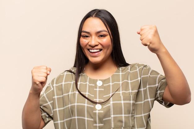 Молодая латинская женщина чувствует себя счастливой, позитивной и успешной, празднует победу, достижения или удачу