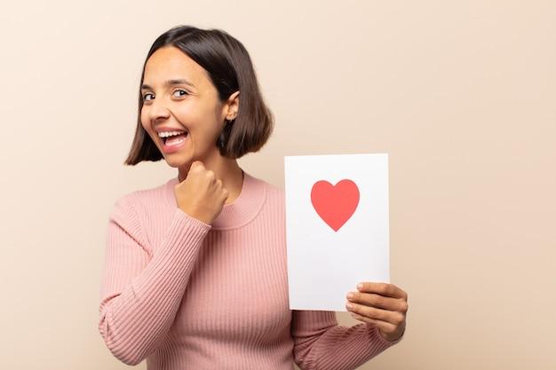 挑戦に直面したり、良い結果を祝ったりするときに、幸せで、前向きで、成功していると感じ、やる気のある若いラテン女性