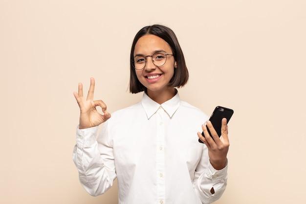 행복하고 편안하고 만족감을 느끼고, 괜찮은 제스처로 승인을 보여주는 젊은 라틴 여자, 미소