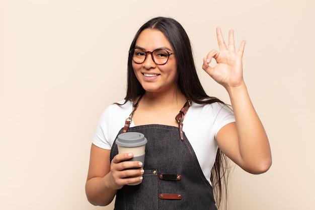 Молодая латинская женщина чувствует себя счастливой, расслабленной и удовлетворенной, демонстрирует одобрение с нормальным жестом, улыбаясь