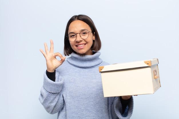 젊은 라틴 여성은 행복하고 편안하며 만족하며 괜찮은 제스처로 승인을 보여주며 웃고 있습니다.