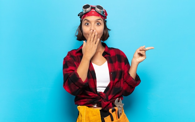 Young latin woman feeling happy, shocked and surprised, covering mouth with hand and pointing to lateral copy space