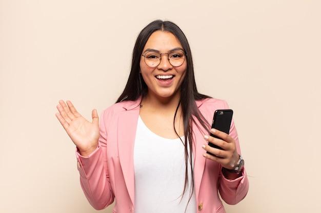 행복하고 놀라움과 쾌활한 느낌, 긍정적 인 태도로 웃고 솔루션이나 아이디어를 실현하는 젊은 라틴 여자