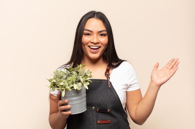 Молодая латинская женщина чувствует себя счастливой, удивленной и веселой
