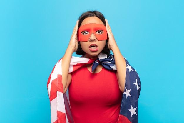 若いラテン女性は恐怖とショックを感じ、手を頭に上げ、間違いでパニックに陥る