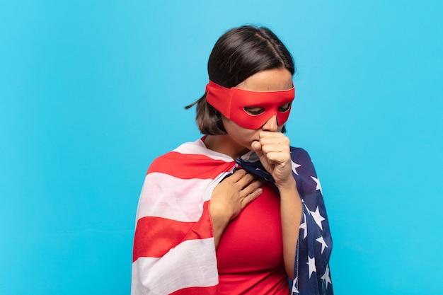喉の痛みとインフルエンザの症状で気分が悪くなり、口を覆って咳をするラテン系の若い女性