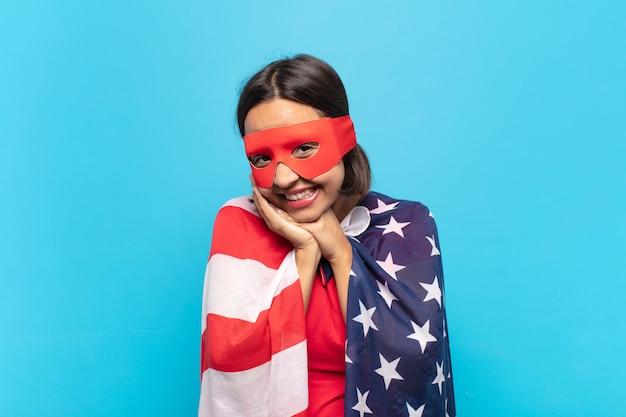 若いラテン女性は恋を感じ、キュートで愛らしい幸せそうに見え、顔の横に手を置いてロマンチックに笑っています