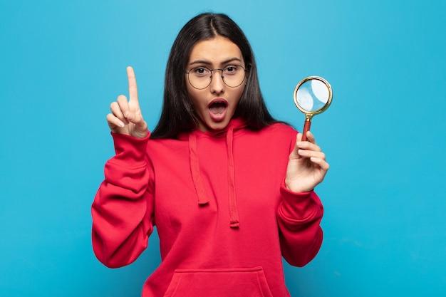아이디어를 깨달은 후 행복하고 신나는 천재가 된 젊은 라틴 여성, 유레카 유레카!
