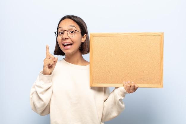 Молодая латинская женщина чувствует себя счастливым и взволнованным гением после реализации идеи, весело поднимая палец