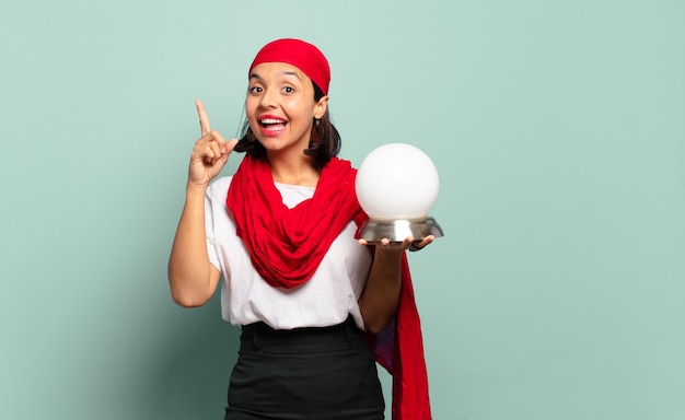 Young latin woman feeling like a happy and excited genius after realizing an idea, cheerfully raising finger, eureka!