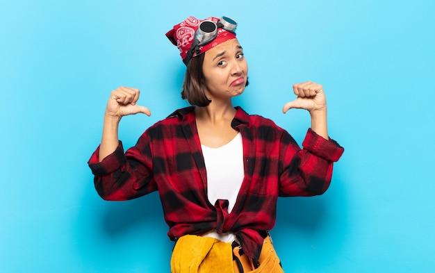 若いラテン女性は、誇り、傲慢、自信を持って、満足して成功しているように見え、自己を指しています