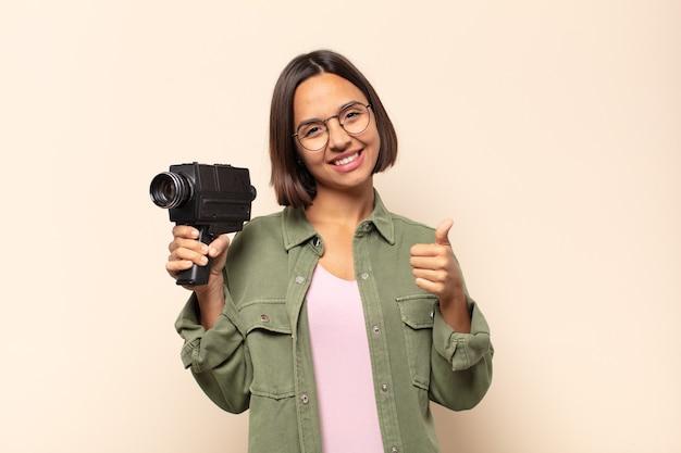 자랑스럽고, 평온하고, 자신감 있고, 행복하고, 엄지 손가락으로 긍정적으로 웃고있는 젊은 라틴 여자