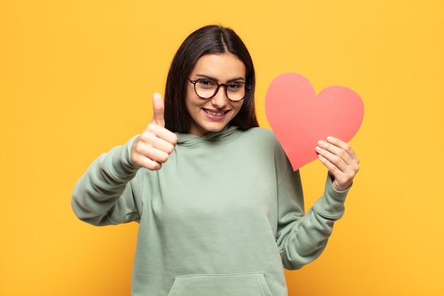 誇り、のんき、自信と幸せを感じ、親指を立てて前向きに笑っている若いラテン女性
