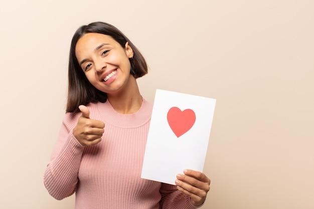 誇り、のんき、自信を持って幸せを感じ、親指を立てて前向きに笑っている若いラテン女性