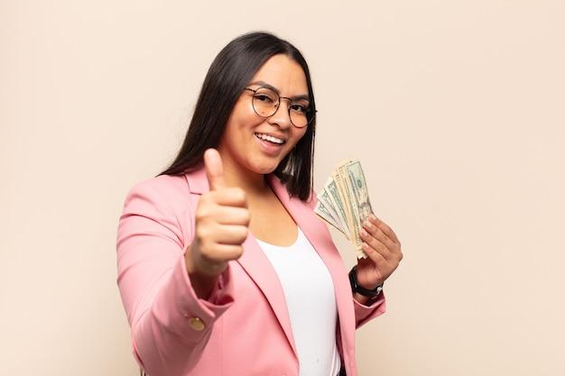 Молодая латинская женщина чувствует себя гордой, беззаботной, уверенной и счастливой, позитивно улыбается с большими пальцами руки вверх