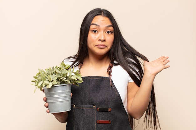 Молодая латинская женщина чувствует себя озадаченной и сбитой с толку, сомневаясь, взвешивая или выбирая разные варианты с забавным выражением лица